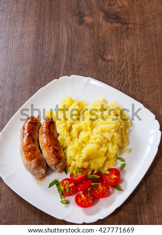 fried meat sausages with mashed potatoes and vegetables salad in a plate on wooden table - stock photo