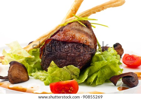 Fried meat with mushrooms and salad leaves on a white dish - stock photo