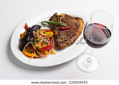 Fried meat with vegetables and red wine - stock photo