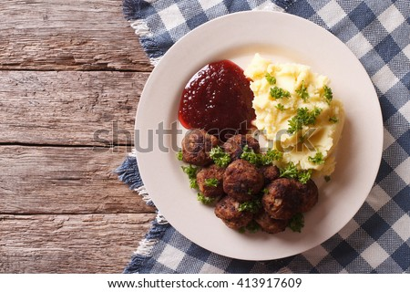 fried meatballs, lingonberry sauce with potato garnish on a plate. horizontal view from above