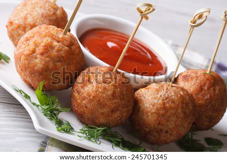 Fried meatballs on skewers and tomato sauce on a plate close-up, horizontal  - stock photo