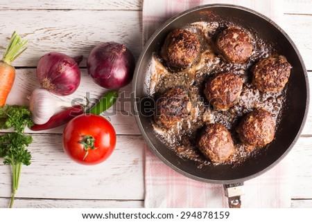 Fried meatballs on the pan and vegetables on the wooden table - stock photo