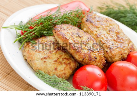 Fried meatballs with dill and tomatoes on a plate - stock photo