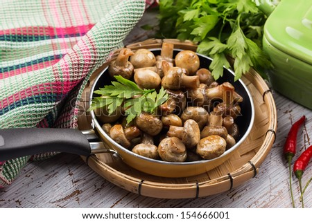 Fried mushrooms in pan  on white table. Selective focus. Rustic style. - stock photo