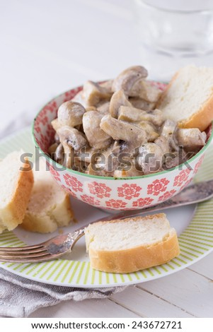 Fried mushrooms   with sour cream on plate on white table. Selective focus. Rustic style. - stock photo