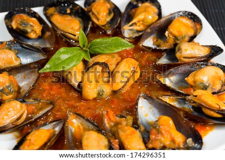Fried mussels in a sauce of fresh tomatoes - stock photo