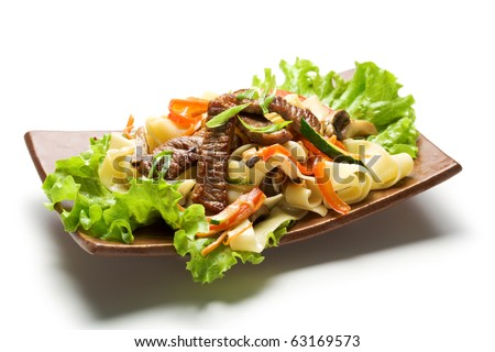 Fried Noodles with Beef and Vegetables. Garnished on Salad Leaf