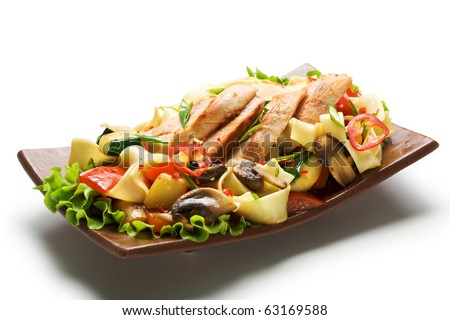 Fried Noodles with Fillet of Chicken and Vegetables. Garnished on Salad Leaf - stock photo