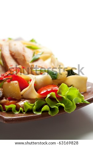 Fried Noodles with Fillet of Chicken and Vegetables. Garnished on Salad Leaf
