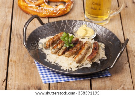 fried nuremberger sausages with sauerkraut  - stock photo