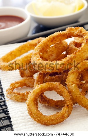 Fried onion rings on absorbent paper, with ketchup and lemon. - stock photo