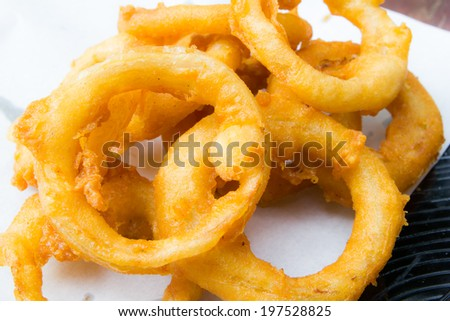 Fried onion rings on dish - stock photo