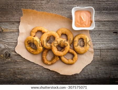 fried onion rings on parchment with sauce on a wooden background - stock photo