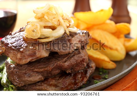 Fried onions on top of a stack of beef steaks. - stock photo