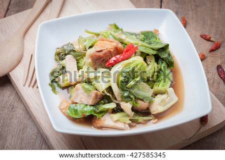 Fried Oyster sauce vegetables sect with crispy pork on wood floors, The national cuisine of Thailand.