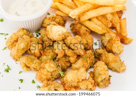 Fried oysters served with French fries and dressing. - stock photo
