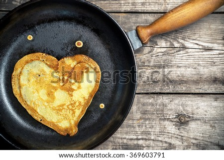 Fried pancakes - heart on a cast iron skillet . Top view . flat lay - stock photo