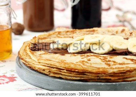 fried pancakes with banana and chocolate on kitchen table background