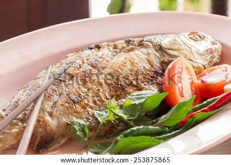 Fried pickled fish , tomato and chili served with fresh vegetable on dish