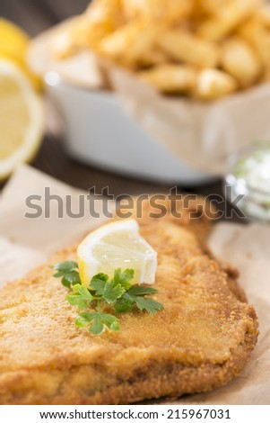 Fried Plaice with french fries (close-up shot) on wooden background - stock photo