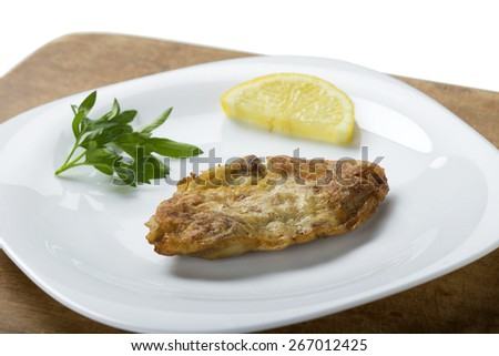 Fried pork brains with lemon and parsley on the plate - stock photo