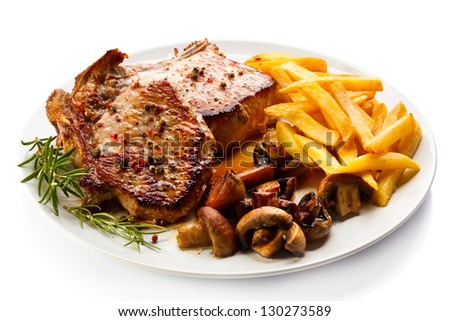 Fried pork chop, chips and vegetable salad - stock photo