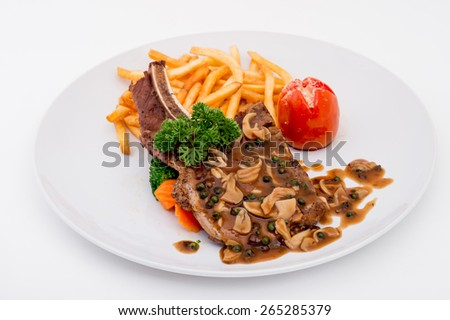 Fried pork chop, chips and vegetable salad,gourmet,A Rib Steak, selective focus on meat. - stock photo