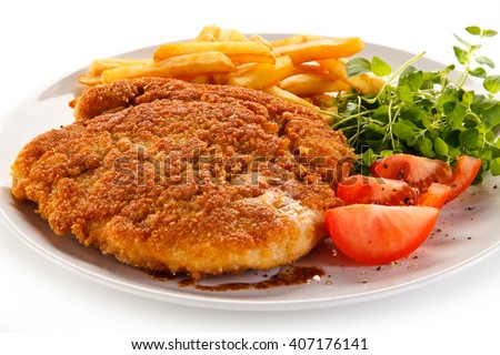 Fried pork chop, French fries and vegetables  - stock photo