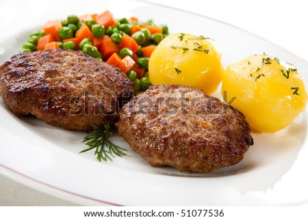 Fried pork chop with boiled potatoes and vegetables - stock photo