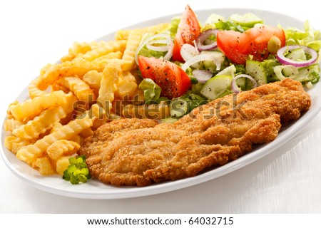 Fried pork chop with chips and vegetable salad - stock photo