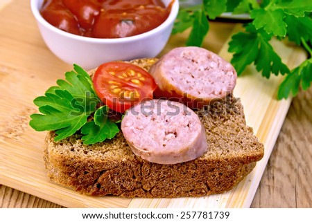 Fried pork sausage on a slice of bread with tomato and parsley, tomato sauce on a wooden boards background - stock photo