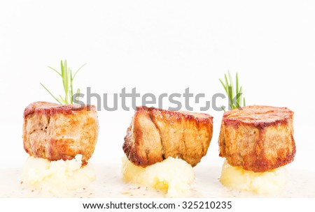 Fried pork tenderloin medallions on mashed potatoes with rosemary and mustard sauce. Macro shot. Photo can be used as a whole background. - stock photo