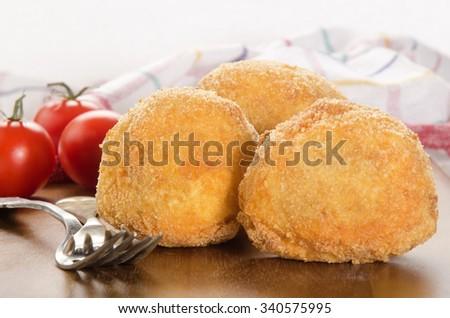 fried potato balls and tomato on wooden board - stock photo