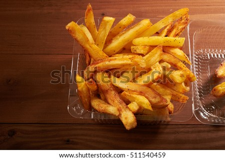 Fried potato chips in plastic packaging on a wooden table