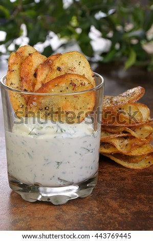 Fried potato chips with spicy sauce served in glass - stock photo