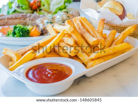 Fried Potato in white dish with tamato sauce - stock photo