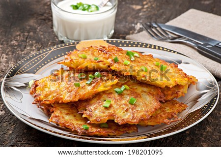 Fried potato pancakes on the old wooden background - stock photo
