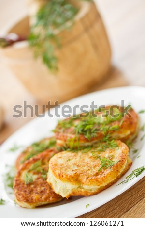 fried potato pancakes with dill on a plate