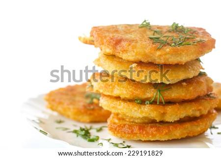 fried potato pancakes with dill on white background - stock photo