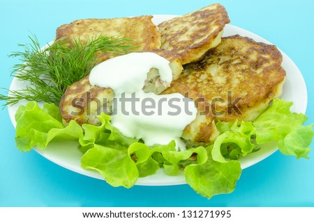 Fried potato pancakes with sour cream, lettuce and greens - stock photo