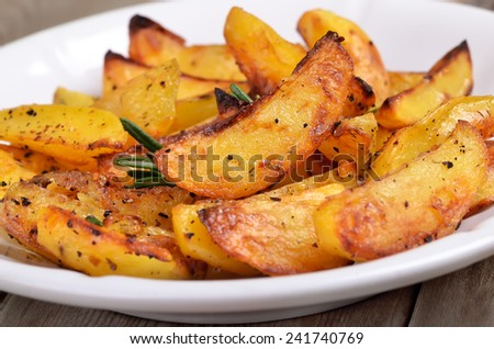 Fried potato wedges on white plate, close up view - stock photo