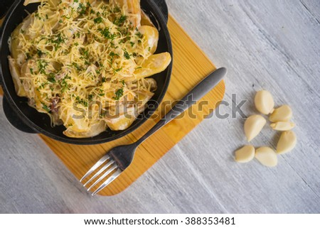 Fried potato wedges with cheese in a pan - stock photo