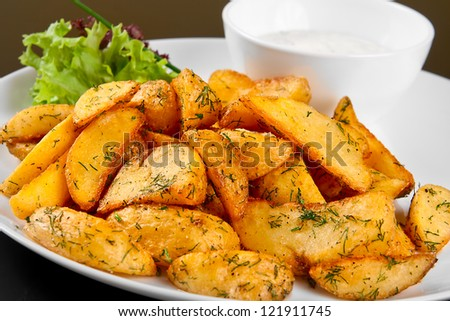 Fried potato wedges with white sauce and lettuce - stock photo