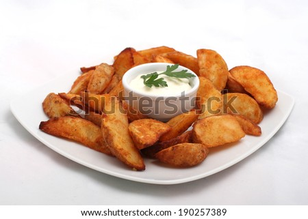 Fried potato wedges with white sauce on white plate - stock photo