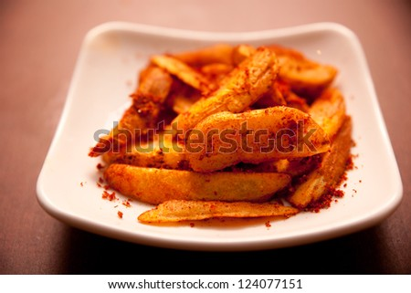 Fried potatoes, and a dish of chili powder
