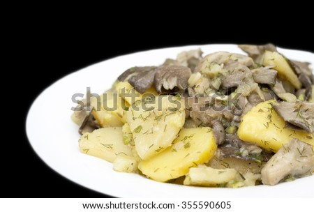 fried potatoes and mushrooms on white plate against black background
