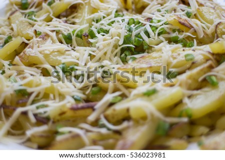 Fried potatoes decorated with green onions and grated cheese.