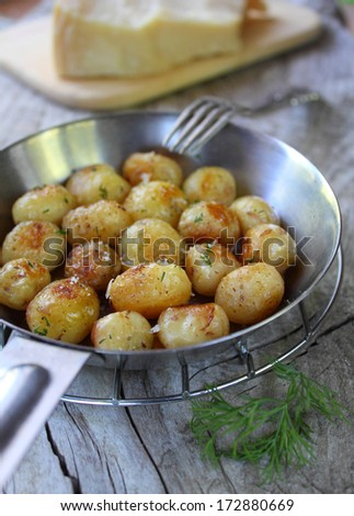 fried potatoes in a pan with cheese and dill - stock photo