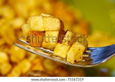 fried potatoes into small cubes on a fork