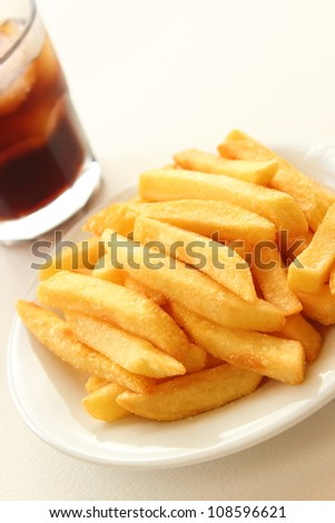 Fried Potatoes on plate and glass of cola - stock photo